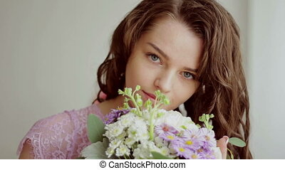 Beautiful girl in a pink dress inhales aroma of a bouquet of flowers. Close-up