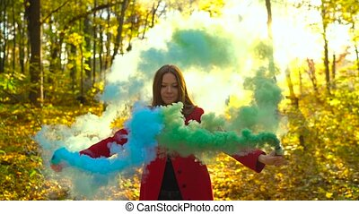 Beautiful girl in a red coat holds colored smoke in her hands and walks through the yellow autumn forest. Slow motion