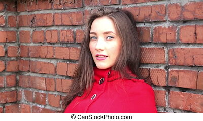 beautiful girl in a red coat on a brick wall background