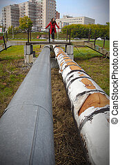 Beautiful girl in a red coat on a large water pipes