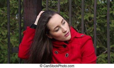 Beautiful girl in a red coat sitting on a brick parapet