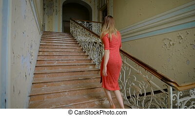 Beautiful girl in a red dress goes up the stairs.