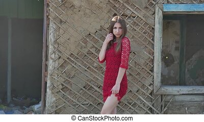 Beautiful girl in a red dress. Sexy girl in a dress is standing next to the old house of the ruins lifestyle