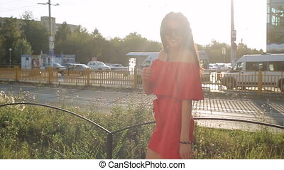 beautiful girl in a red dress walking in the city