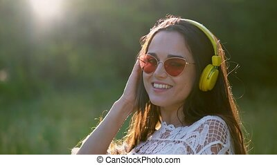 Beautiful Girl in a Romantic Image Lis Tens to Headphones with Pleasant Music.