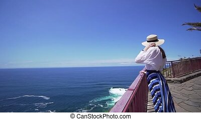 Beautiful girl in a stylish hat on the edge of a cliff looking at the Atlantic Ocean. Canary Islands, Spain