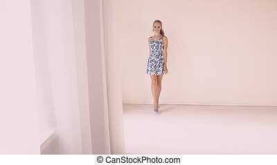beautiful girl in a summer dress in white room