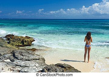 Beautiful girl in a swimsuit on the sea. Woman with a beautiful figure in swimsuit on the tropical beach.