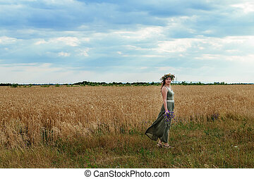 beautiful girl in a wheat field with  wreath on head