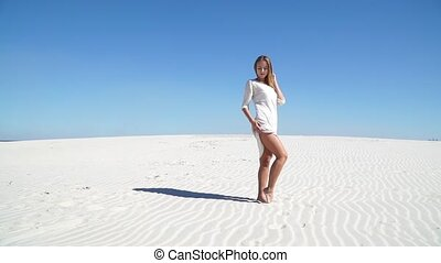 Beautiful girl in a white dress standing in the desert