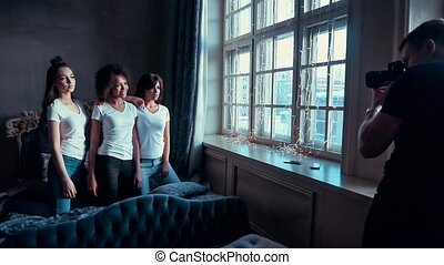 Beautiful girl in a white T-shirt posing at a photo shoot.