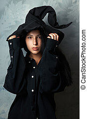 girl in a witch costume looks mysteriously