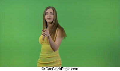 Beautiful girl in a yellow dress, on a green screen. She turns and makes a gesture with her hand.