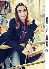 Beautiful girl in amusement park. Carousel