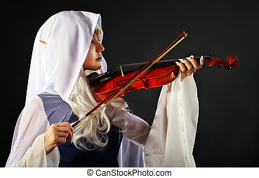 Beautiful girl In an elf costume with a violin on a gray background. Original cosplay character