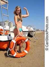 Beautiful girl in bikini with lifebuoy shows power