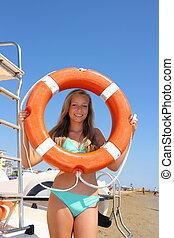 Beautiful girl in bikini with lifebuoy smiles