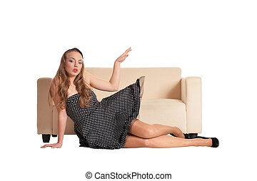 Beautiful girl in black dress posing near sofa