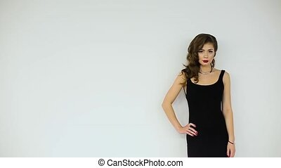 Beautiful girl in black dress posing on a white background