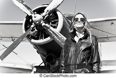 Beautiful girl in black jacket standing on a war aircraft. -...