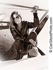 Beautiful girl in black jacket standing on a war aircraft....