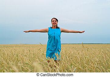girl in blue dress in rye field