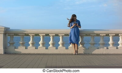 Beautiful girl in blue dress using digital tablet.
