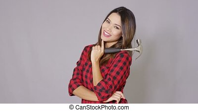 Beautiful girl in checkered shirt with hammer - Beautiful...