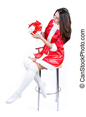 beautiful girl in Christmas dress holding a present sitting on a chair