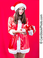 girl in Christmas dress with a gift on a red background