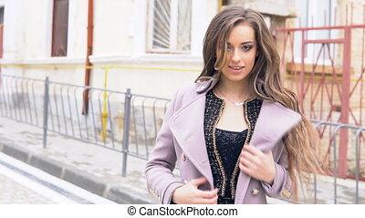 beautiful girl in coat posing smiling outdoors