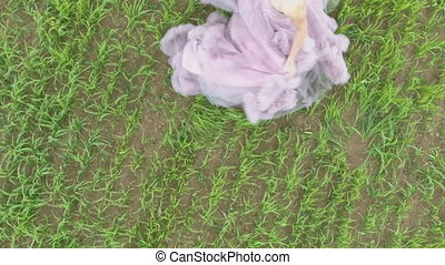 Beautiful Girl in dress enjoying nature on a spring field.