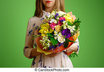 Beautiful girl in dress holding a bouquet of different flowers. Isolated