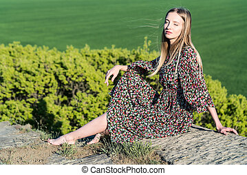 Beautiful girl in dress poses on rock in nature