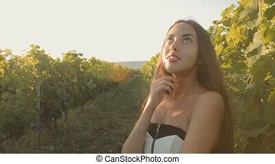 Beautiful girl in dress posing near the vineyards