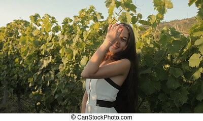 Beautiful girl in dress posing near the vineyards