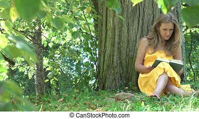 beautiful girl in dress reading book sitting under tree take books and hat and walk away. 4K