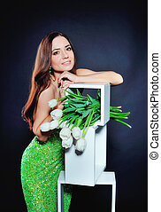 Beautiful girl in evening dress with green tulips