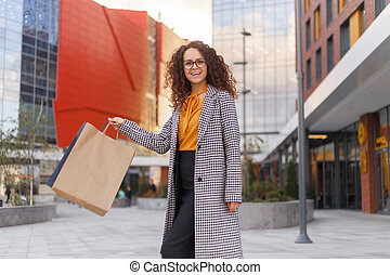 Beautiful girl in eyeglasses is holding shopping bags, looking at camera and smiling while walking down the street.