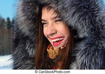 Beautiful girl in fur coat with hood laughs outdoor