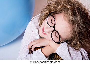 Beautiful girl in glasses with eyes closed dreaming.