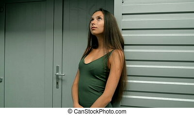 beautiful girl in green dress stands near a metal wall