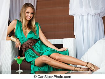 Beautiful girl in green dress with cocktail on summer terrace