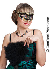 Beautiful girl in green evening dress with necklace and earrings in carnival mask hodling fan
