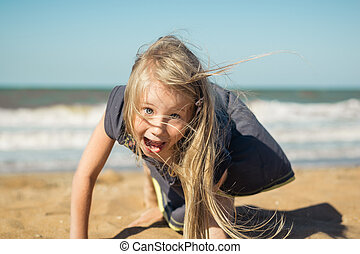 Beautiful girl in grey dress makes a cheerful face on the sand of the sea.