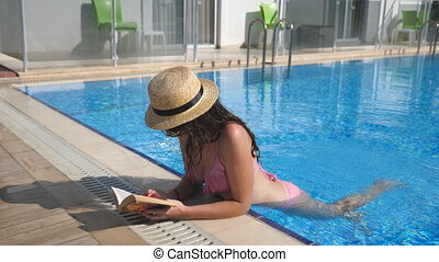 Beautiful girl in hat and sunglasses reading book at pool....