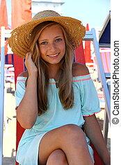 Beautiful girl in hat on beach