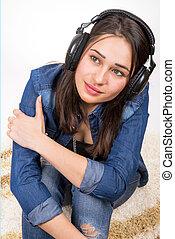 girl in headphones sitting on the carpet