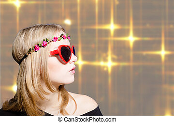 Beautiful girl in heart shaped sunglasses on bokeh background