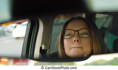 Beautiful girl in in glasses paints lips in the car and...